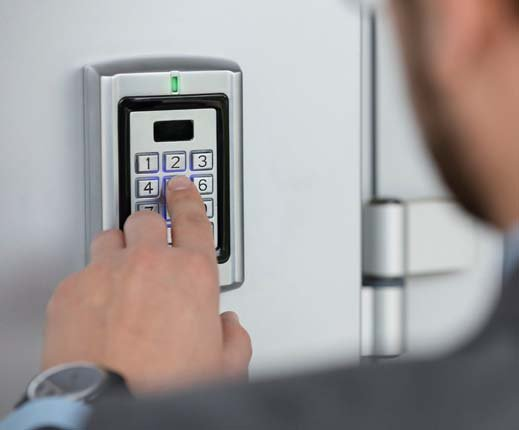man inputting code to keypad entry security device