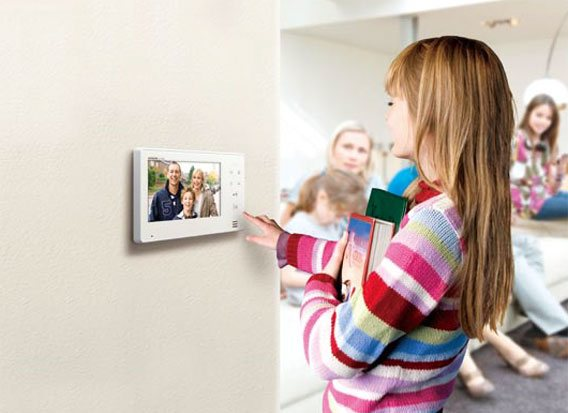 little girl interacting with video intercom device inside the house